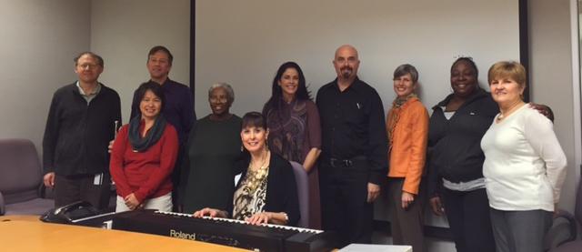 UCOP Singers rehearse: Back row (left to right) — Chris Hanson, George Lemp, Kim Williams, Julia Arno, Daniel Scuiry (director), Sandra Wulff, Ishtar Peeler, Linda Kane. Front row — Regina Ranoa, Gail Lew at piano