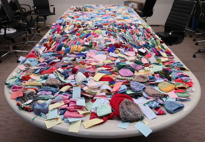 Hundreds of tiny hats on table