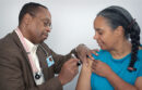 Medical professional giving woman flu vaccine