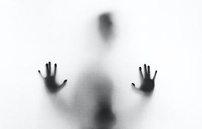Dark silhouette behind glass wall